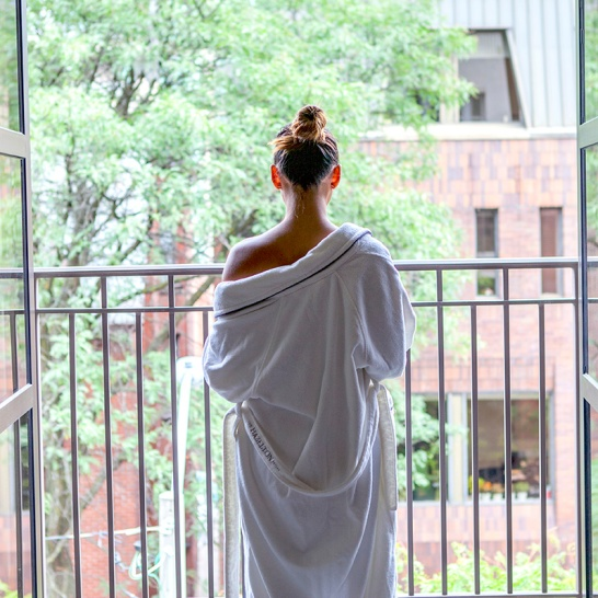 female standing on the balcony in a Hazelton Hotel robe