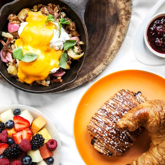 Eggs benedict, bowls of fruits, croissants and jam