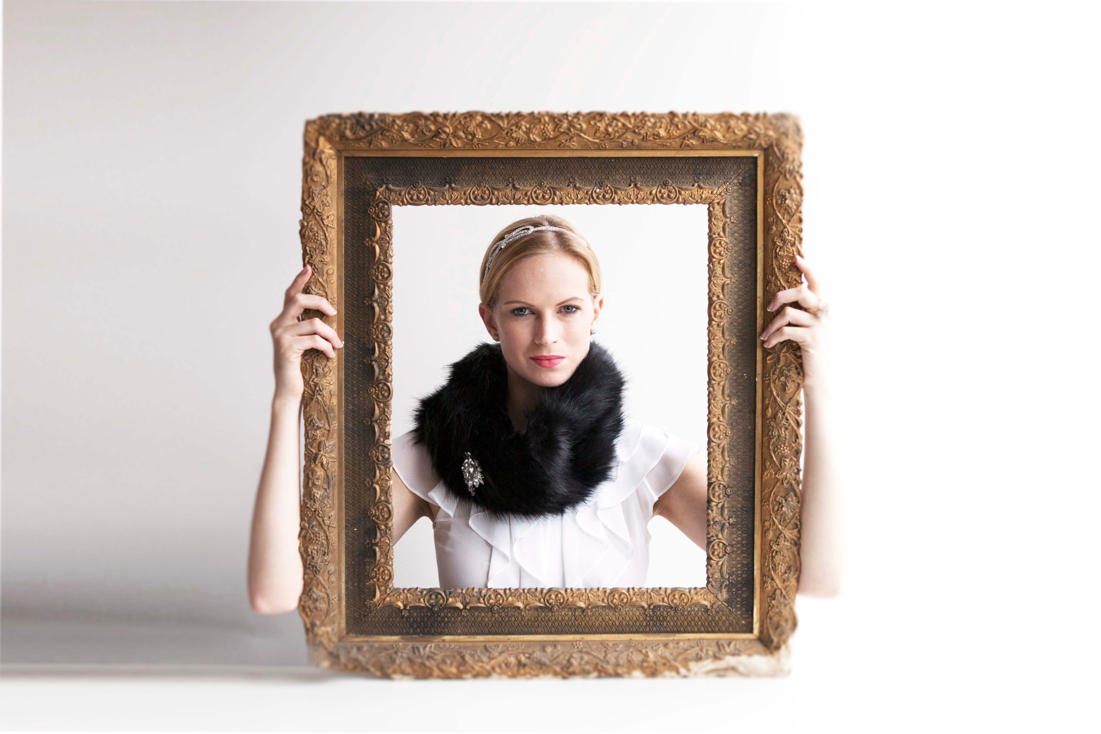 Model wearing diamond bow head band, black fur collar with brooch and white ruffle shirt hold vintage picture fram