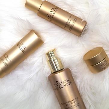 Facial brand l'Elixir Des Glacier's in gold packaging on white fur background