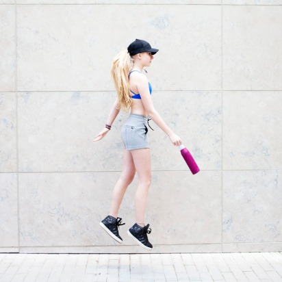 Female jumping high in lululemon bra and shorts