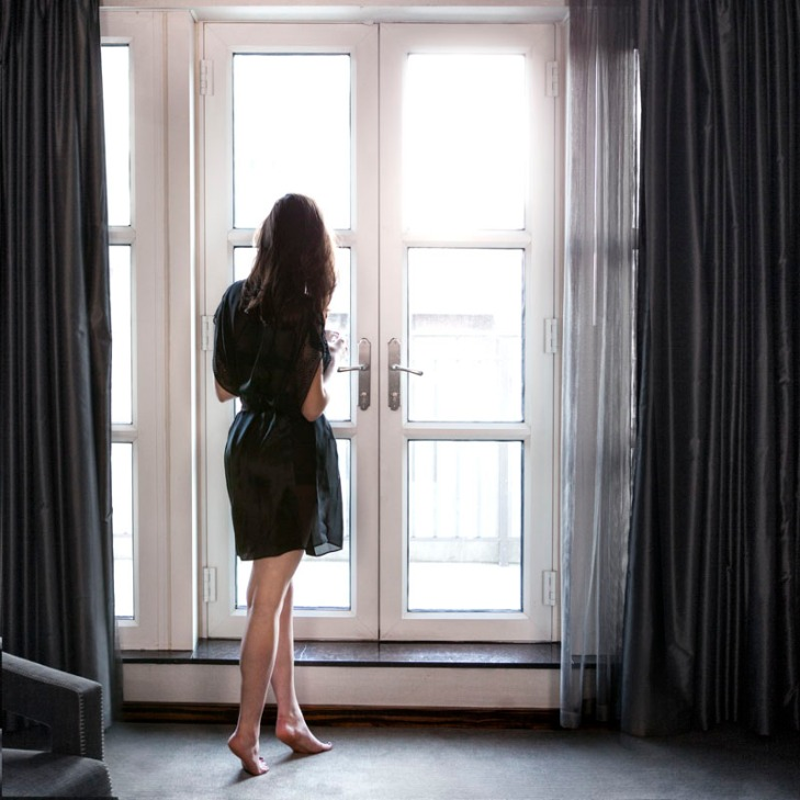 Female looking through doors at the Hazelton Hotel in Toronto