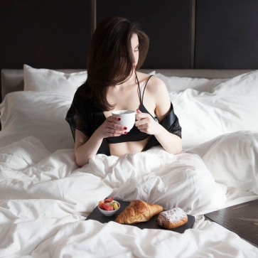 Female sitting in a puffy bed drinking coffee and eating crossants