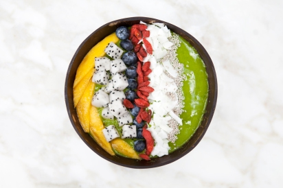 A Bowl of smoothie with mangos, dragon fruit, berries and coconut on top
