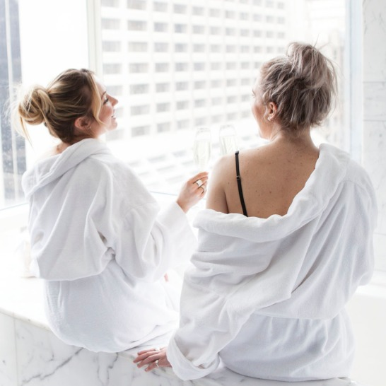 Two females in robes drinking wine and overlooking the city
