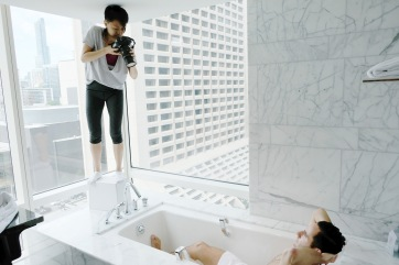 Photographer standing on a cube in the bathroom