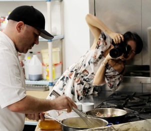 Chef working over a grill and Jiali taking photos super close up