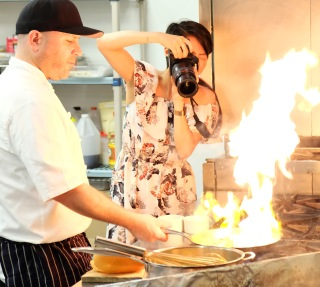 Chef working over a grill and Jiali taking photos of the flames