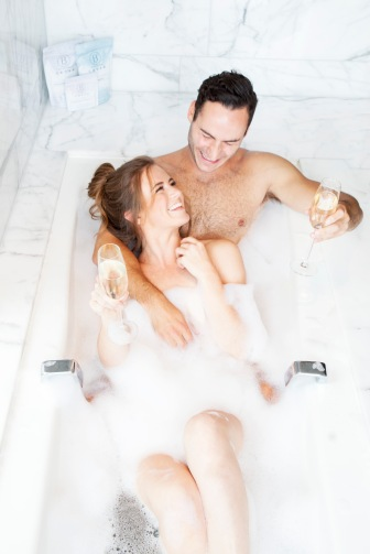 couple in a bath tube laughing