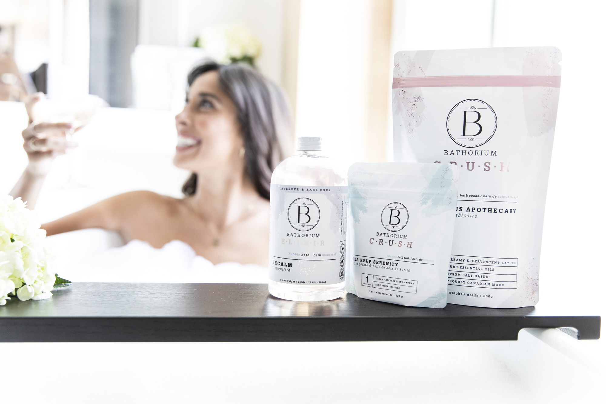 Bathorium Becalm, Sea Kelp Serenity bath soak, and Eucalyptus Apothecary with woman in the background in a tub