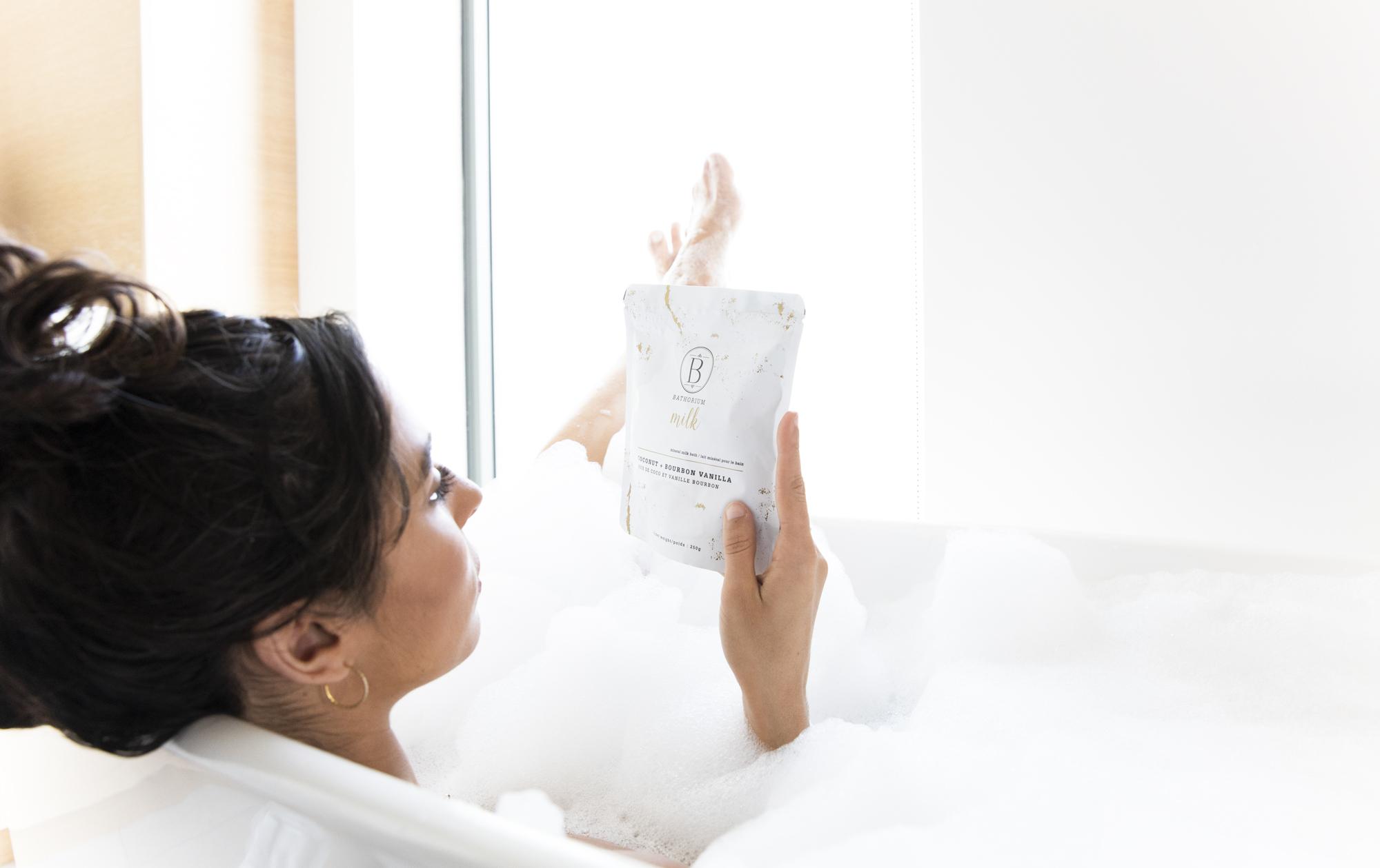 Woman in a tub holding a bag of Bathorium Milk bag