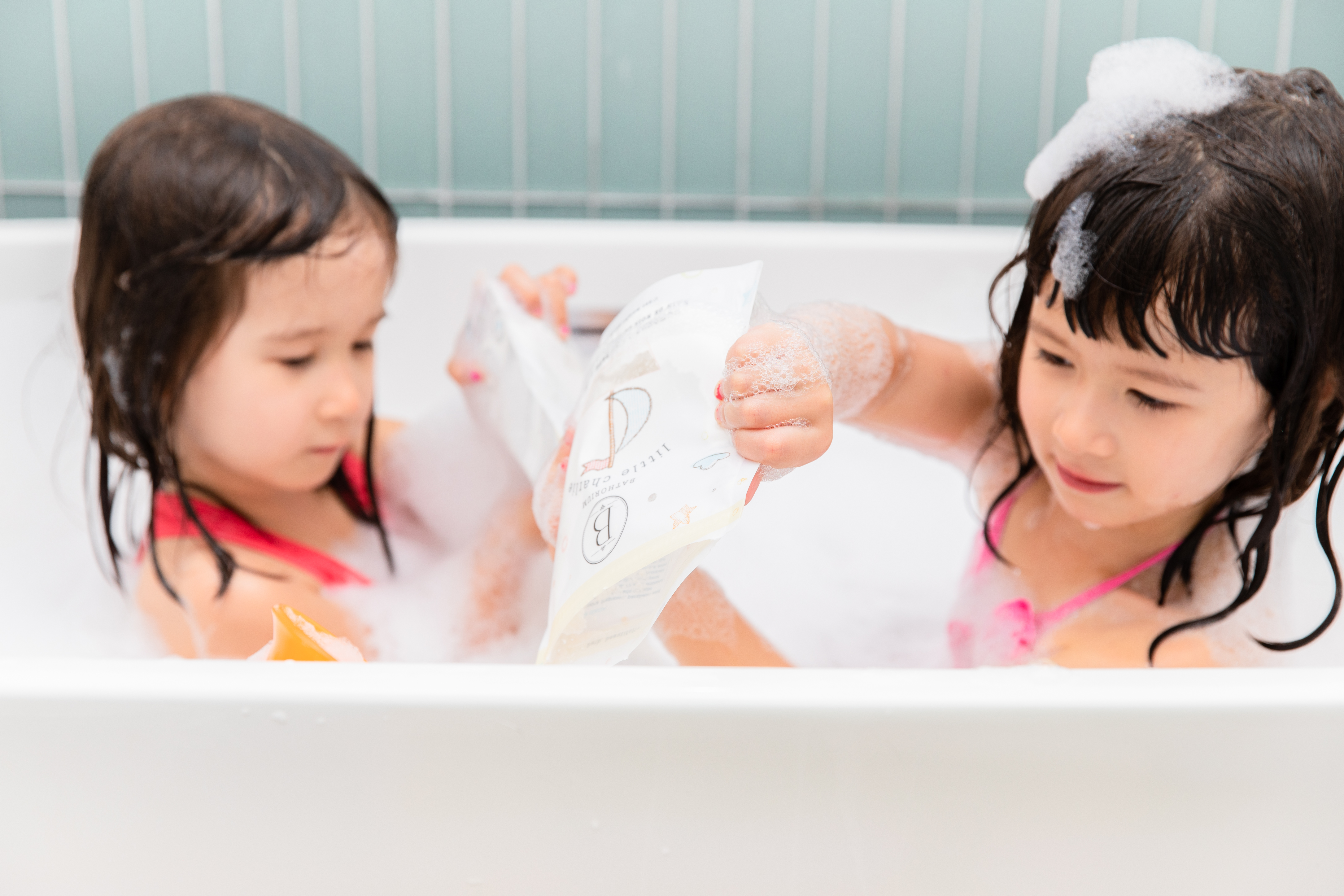 Two little girls playing with Little Charlie bath soak bags