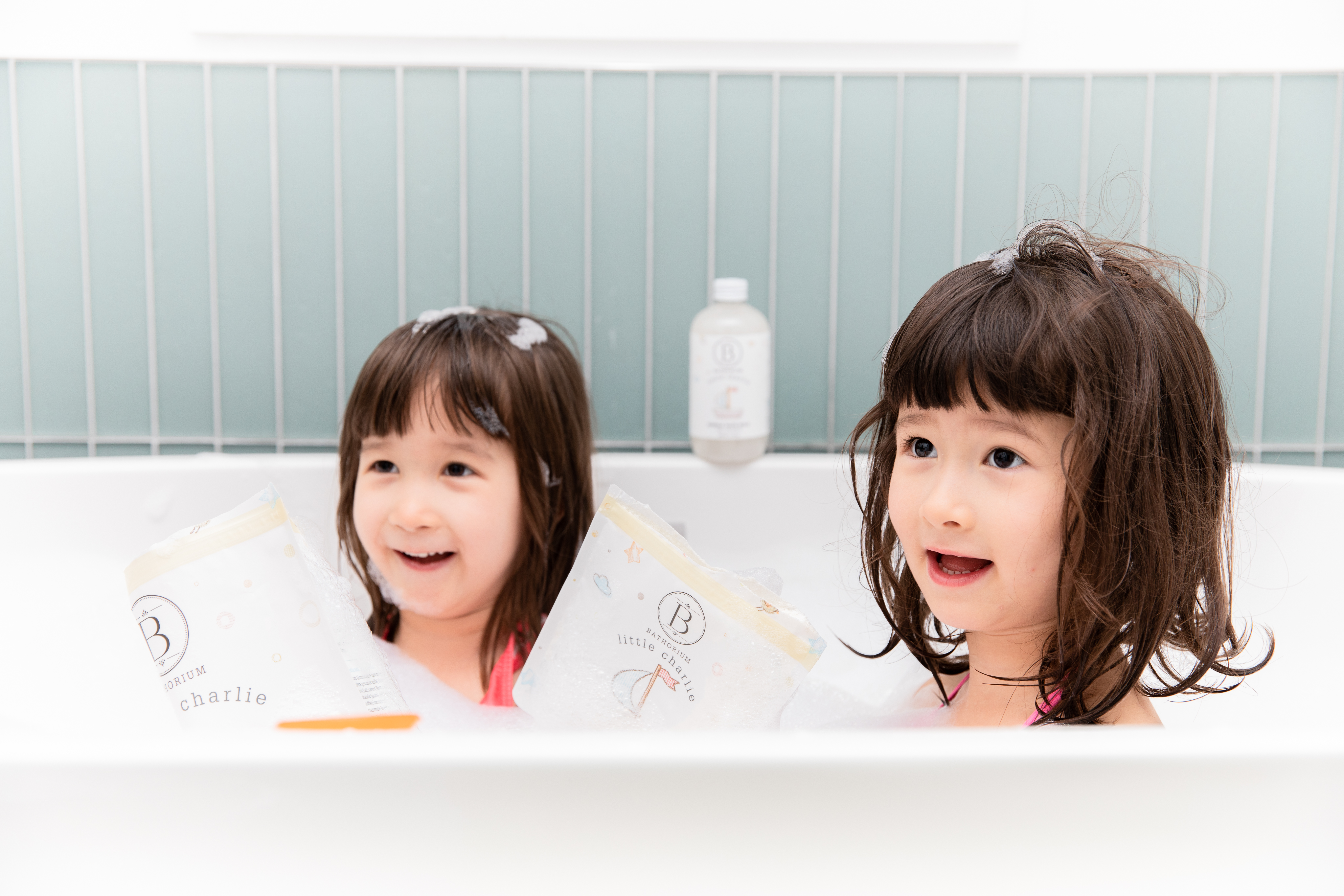 Two little girls in tub playing with Little Charlie Bath Soak
